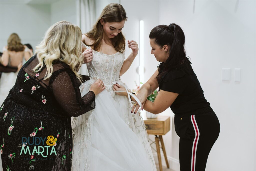 bride trying on lace wedding dress at bridal shop with the help of two employees in black - bridal finery orlando wedding gowns