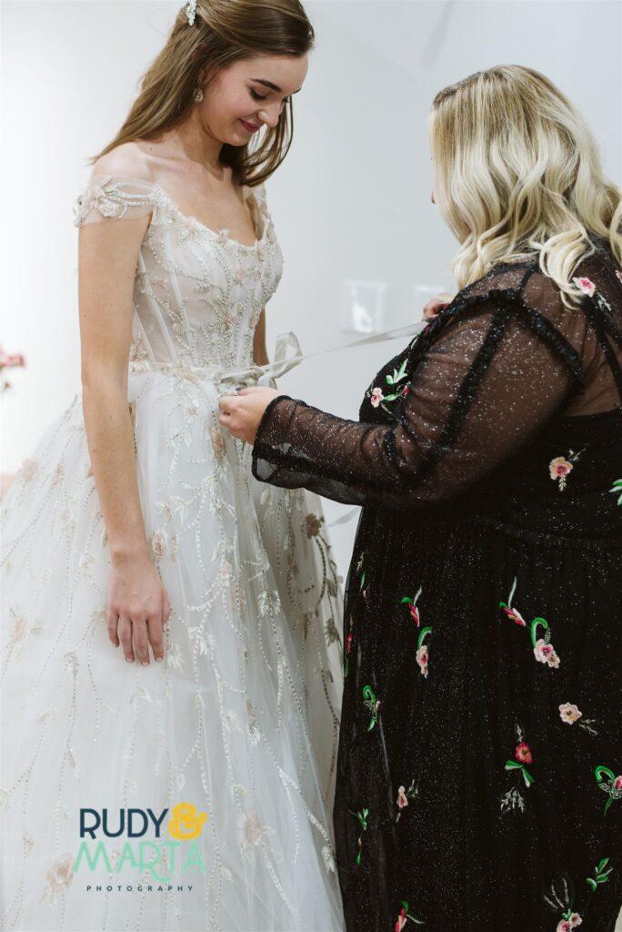 woman in black dress helping to fasten wedding dress on woman in bridal shop - bridal finery orlando wedding gowns