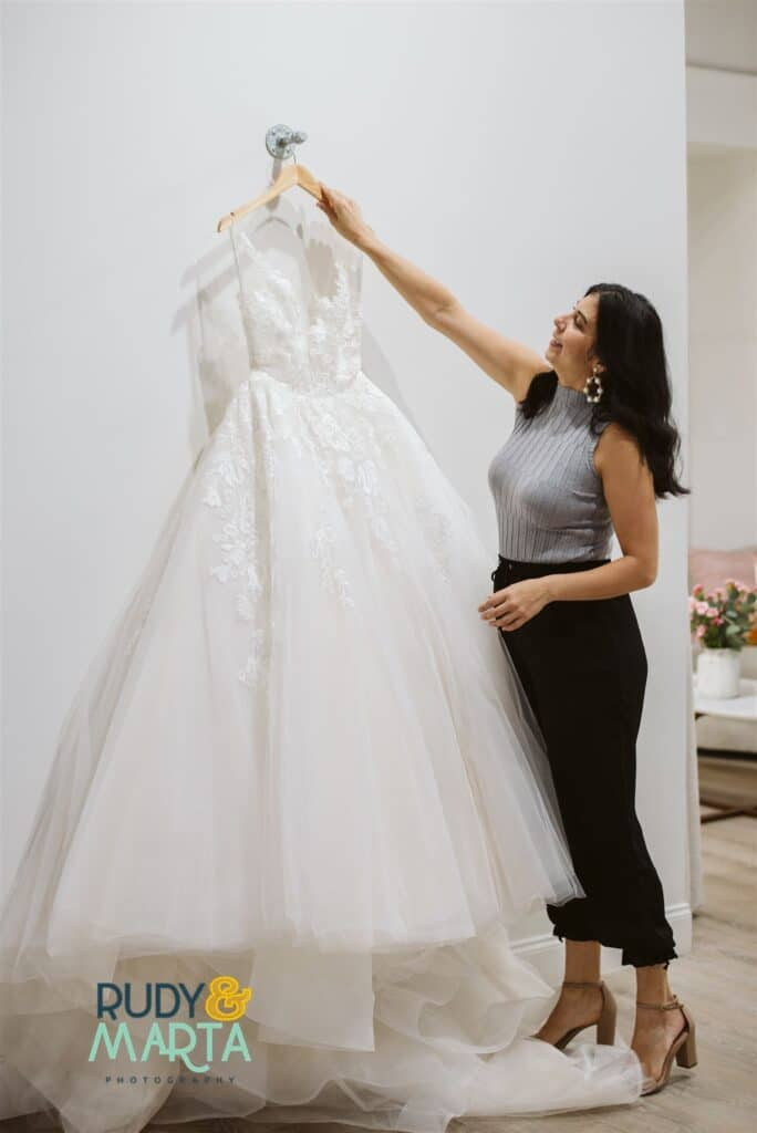 woman in gray and black placing wedding dress onto hook on white wall in bridal shop - bridal finery orlando wedding gowns