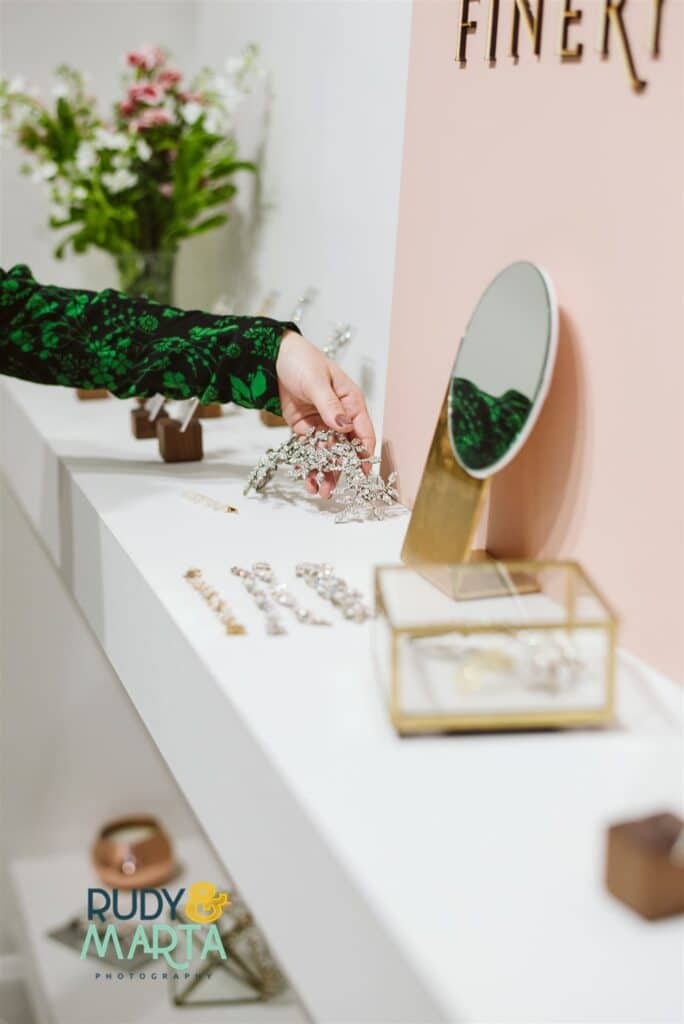 woman's hand with green and black sleeve reaching for jewelry in pink and white room - bridal finery orlando wedding gowns