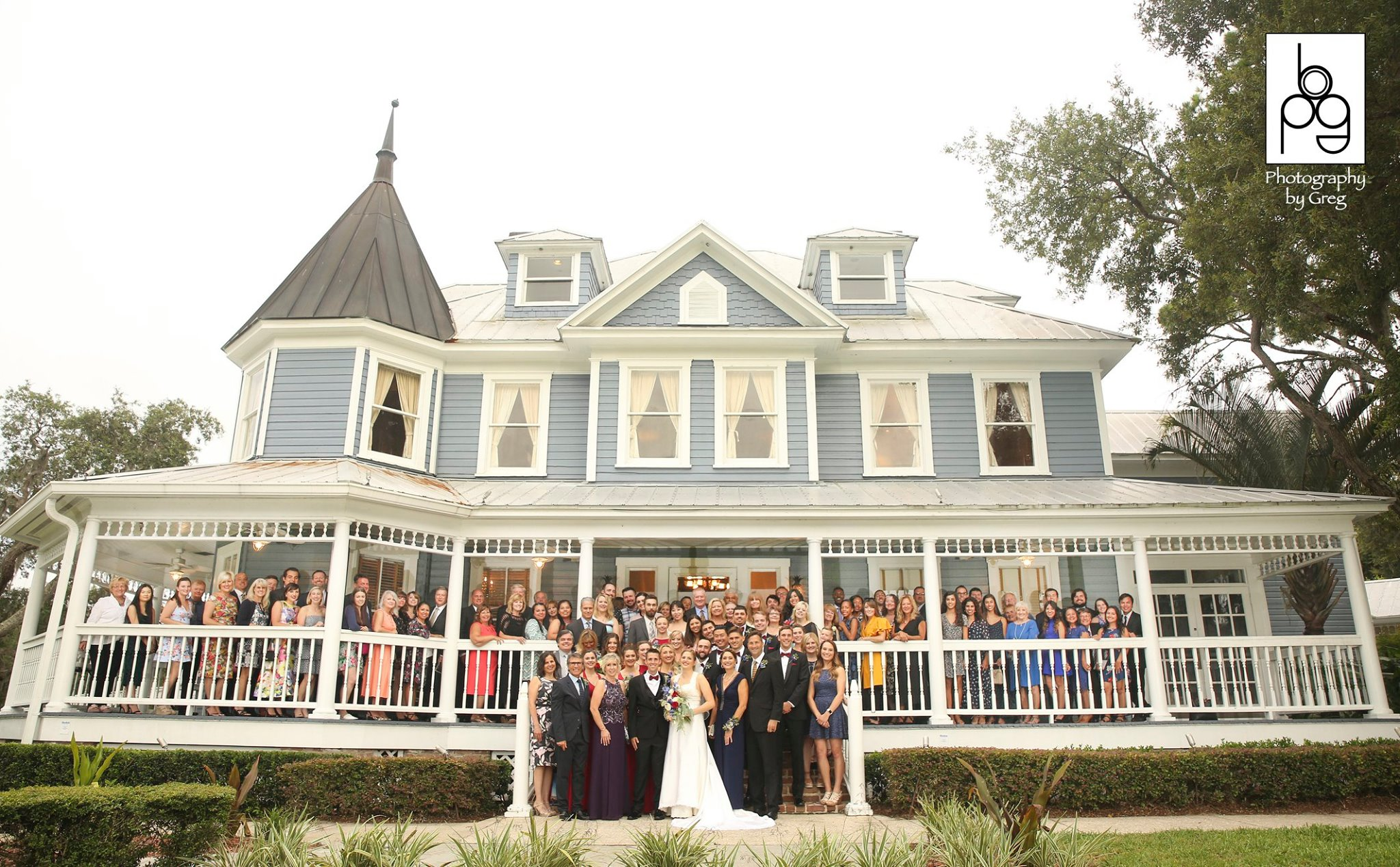 P.S. I Love You Productions, all the guests and bridal party standing on the porch of a house