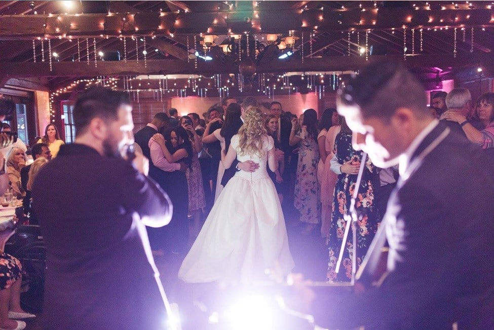 P.S. I Love You Productions, bride and groom dancing in the background with band playing