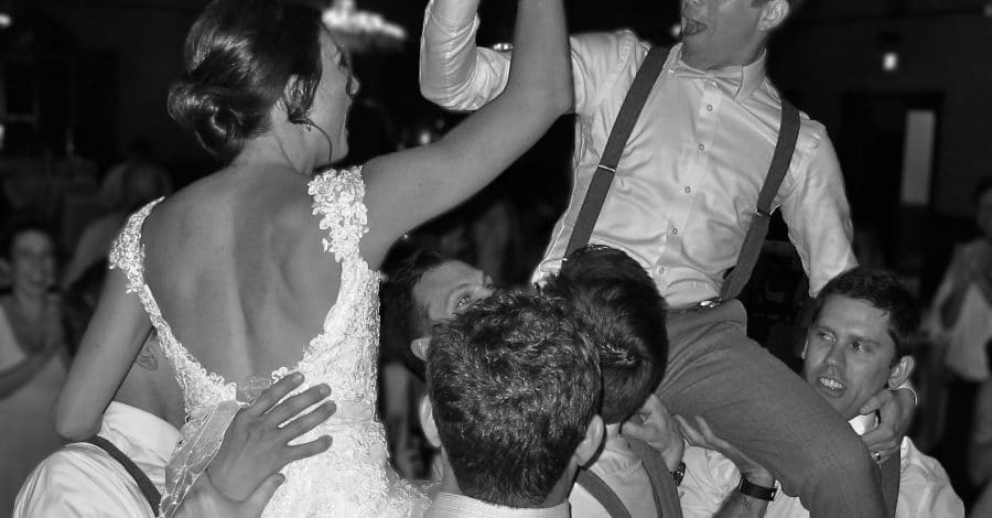 Classic-Disc-Jockeys-Bride and Groom giving high five while being lifted up by groomsmen at reception