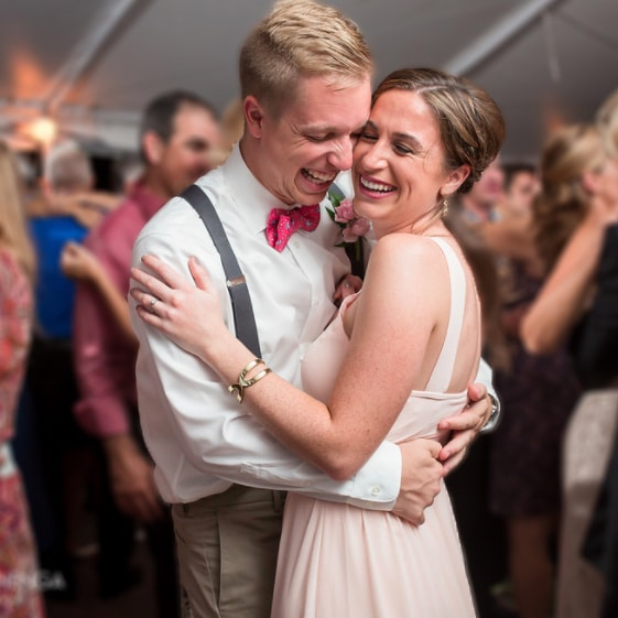 Bride and groom laughing with arms around each other