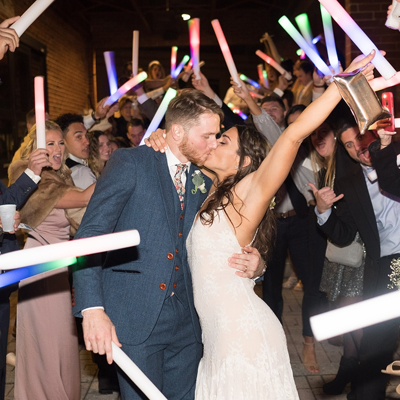 newlyweds kiss while guests cheer with glow sticks