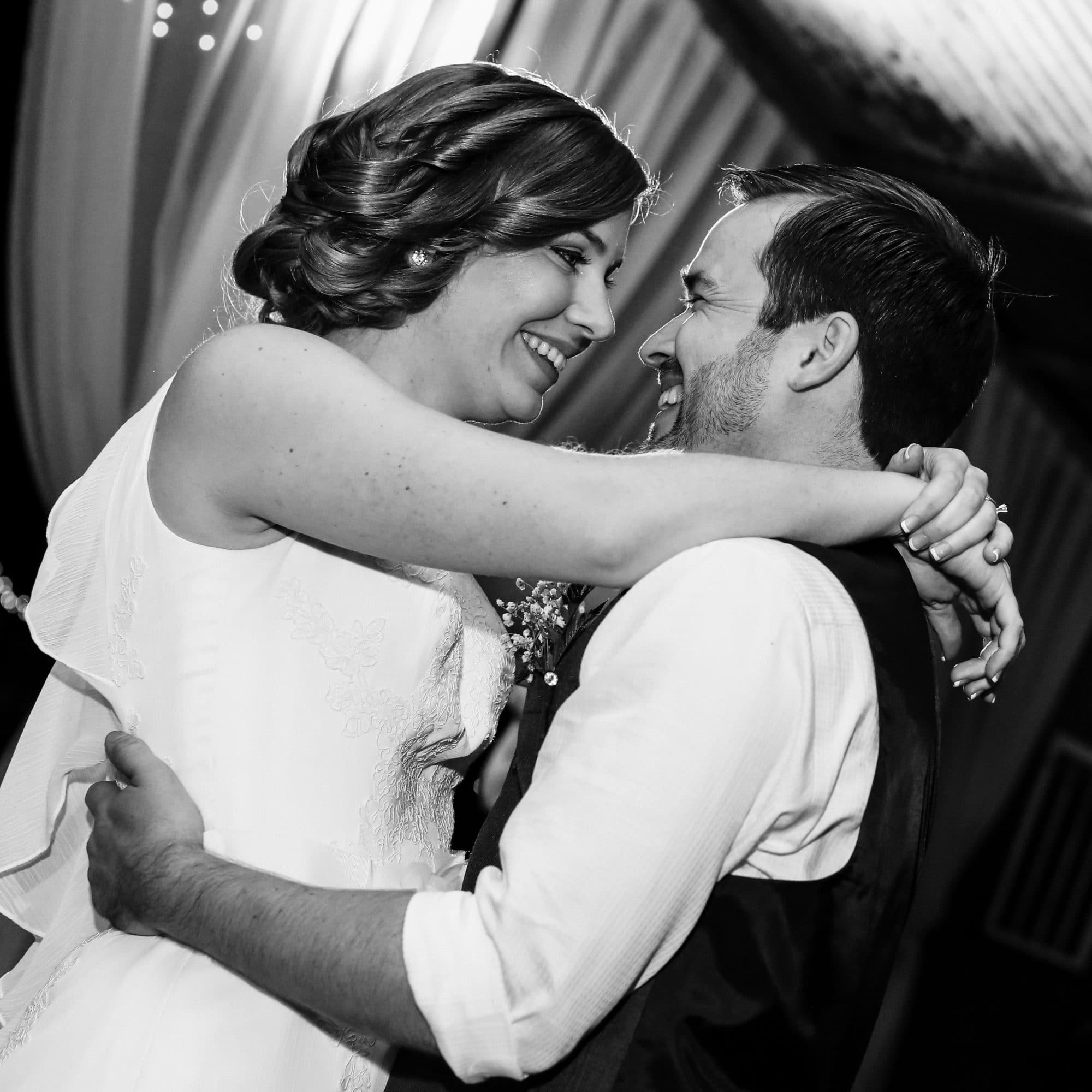 Black and white photo of bride and groom smiling during first dance