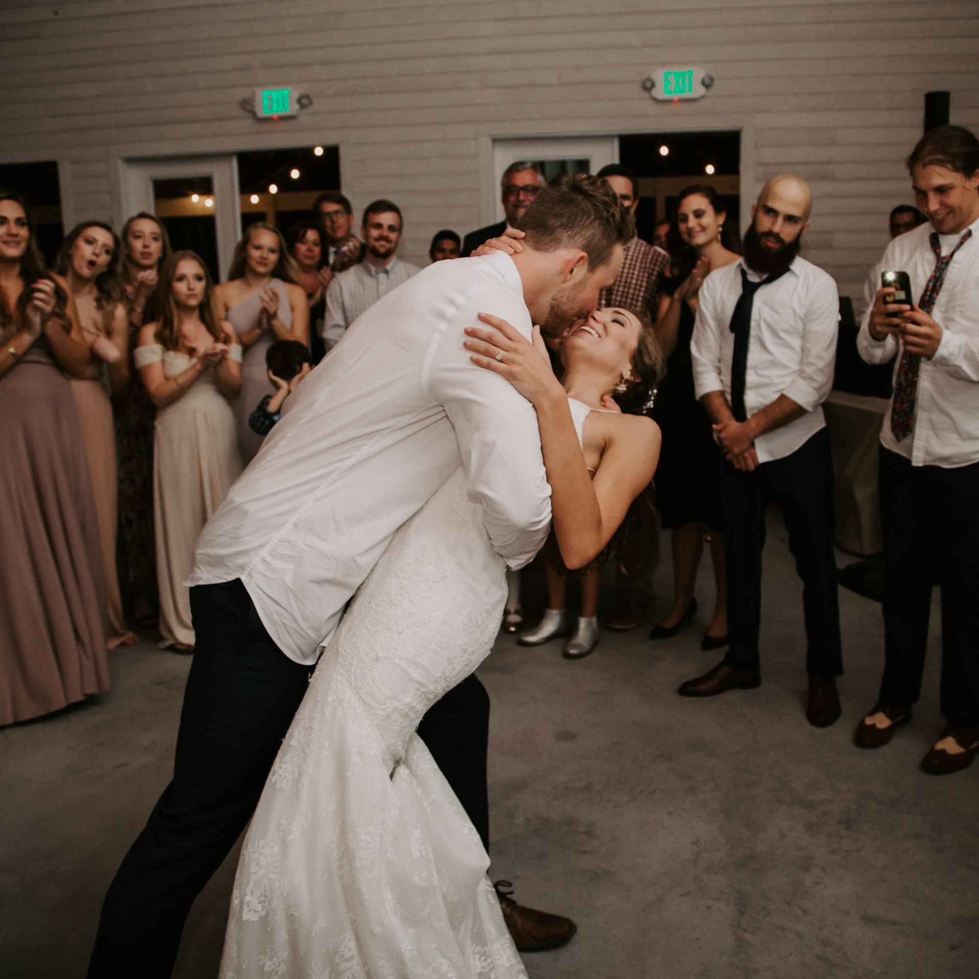 Groom dipping bride on the dance floor at wedding reception
