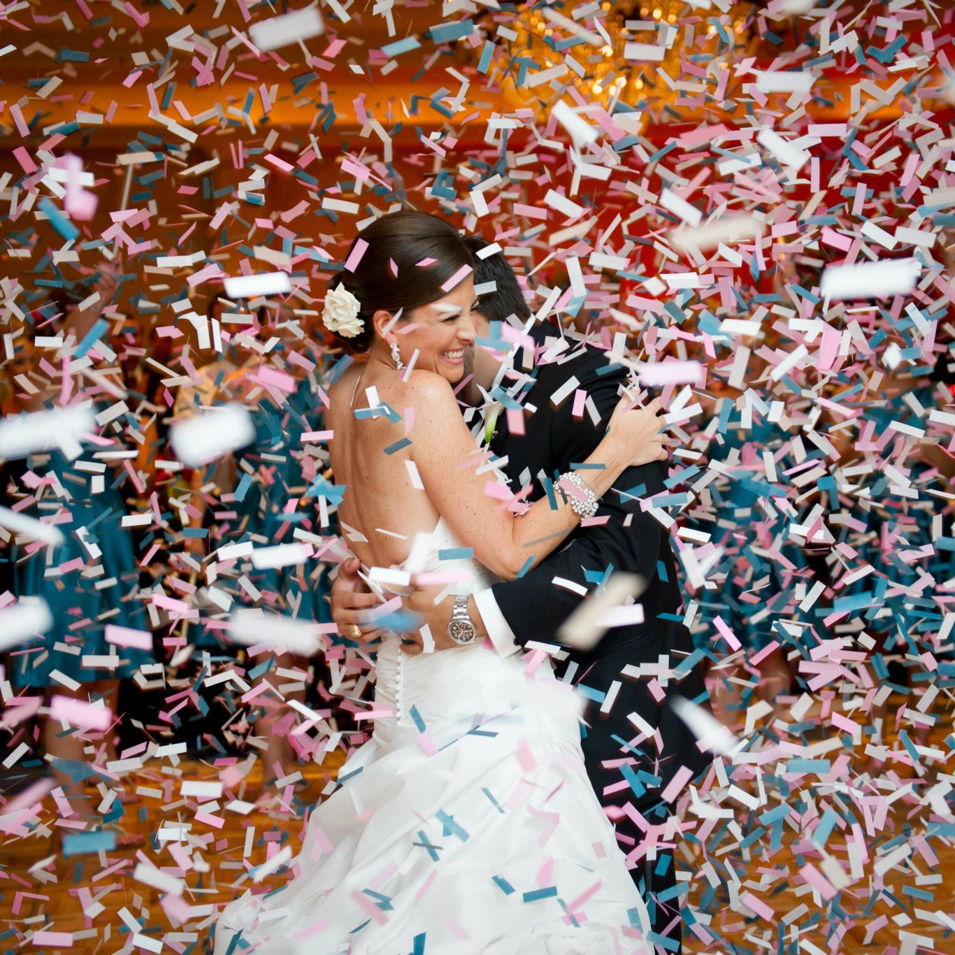 Smiling bride and groom hugging in shower of confetti
