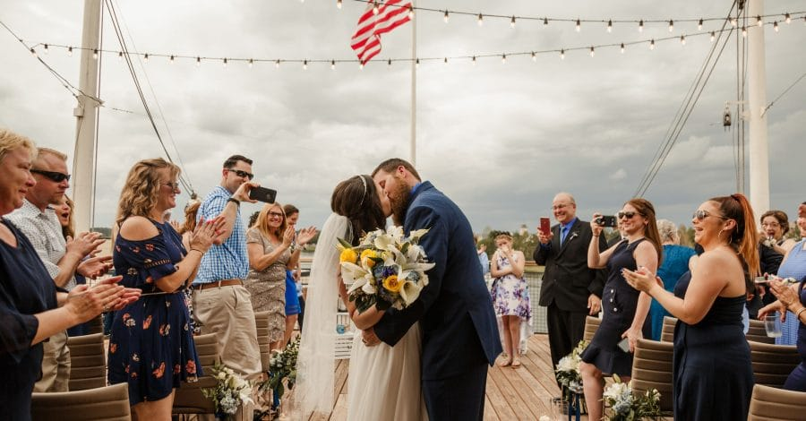 For the Love of Events - Newlyweds kissing on dock in front of wedding guests