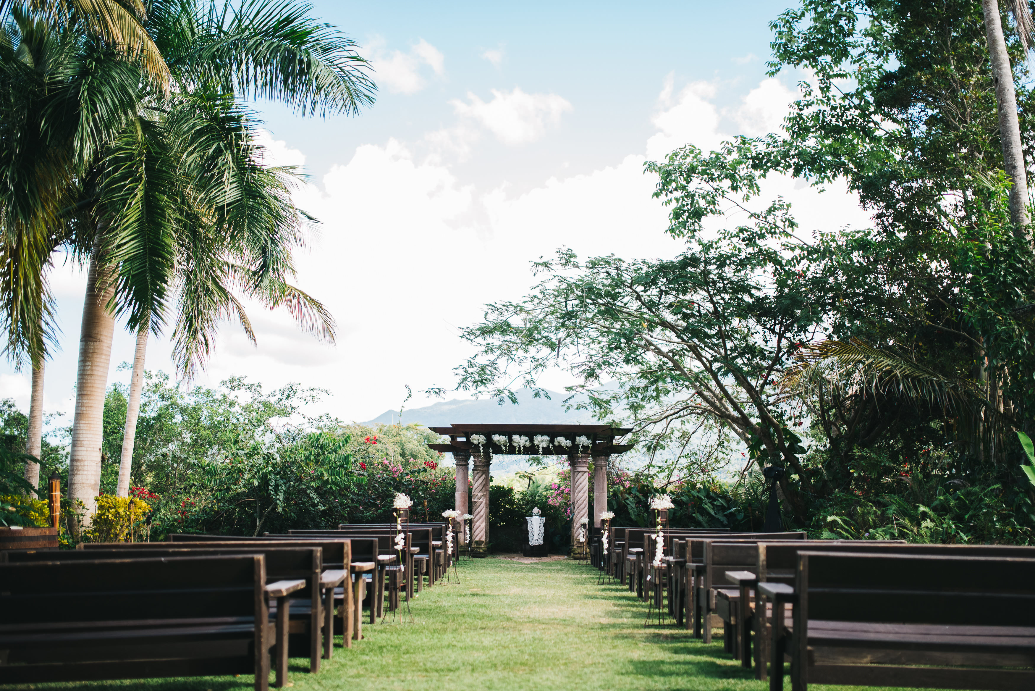 Rudy & Marta Photography - outdoor wedding ceremony setup with pews and pergola