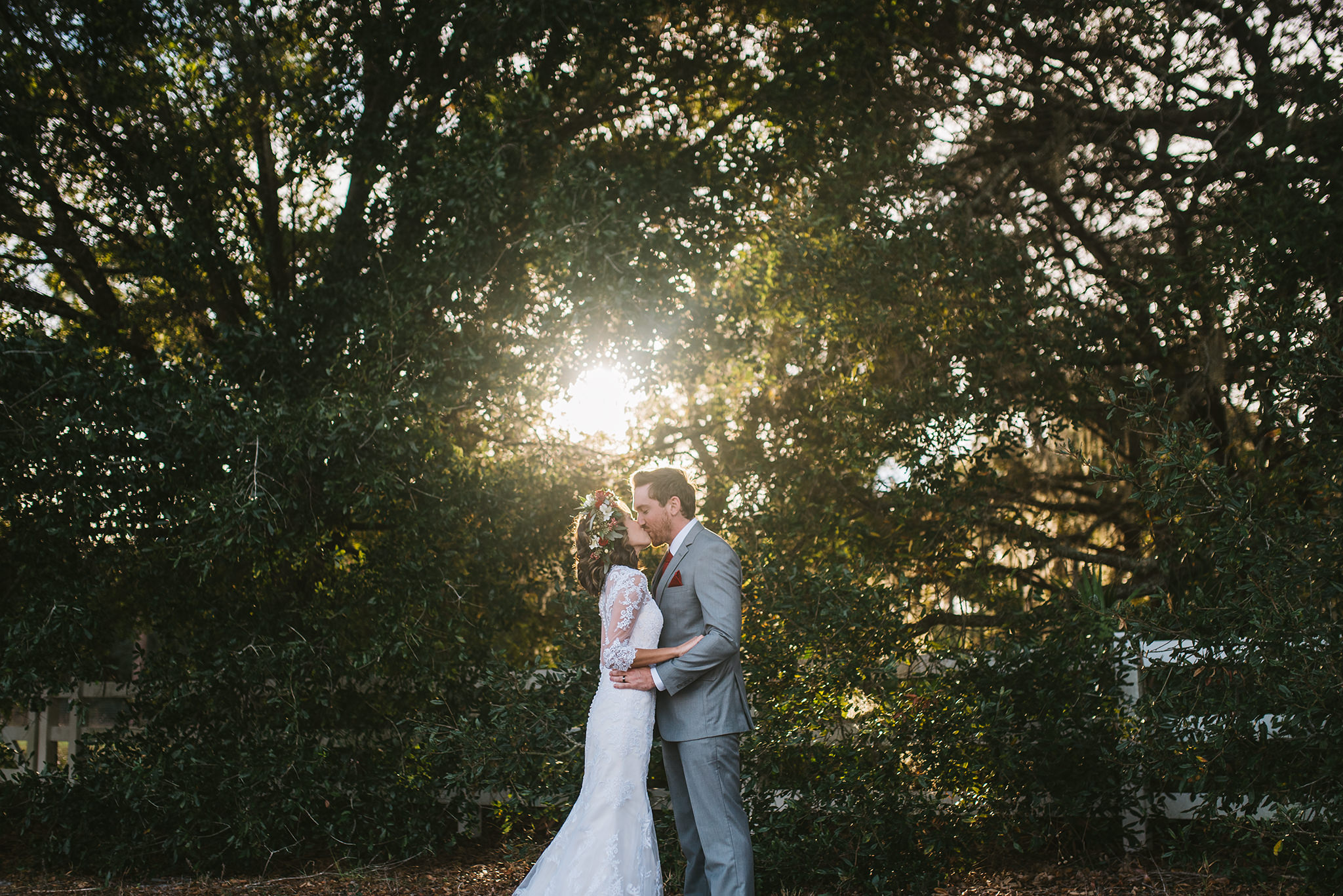 Rudy & Marta Photography - bride and groom kiss with sunlight through the trees behind them
