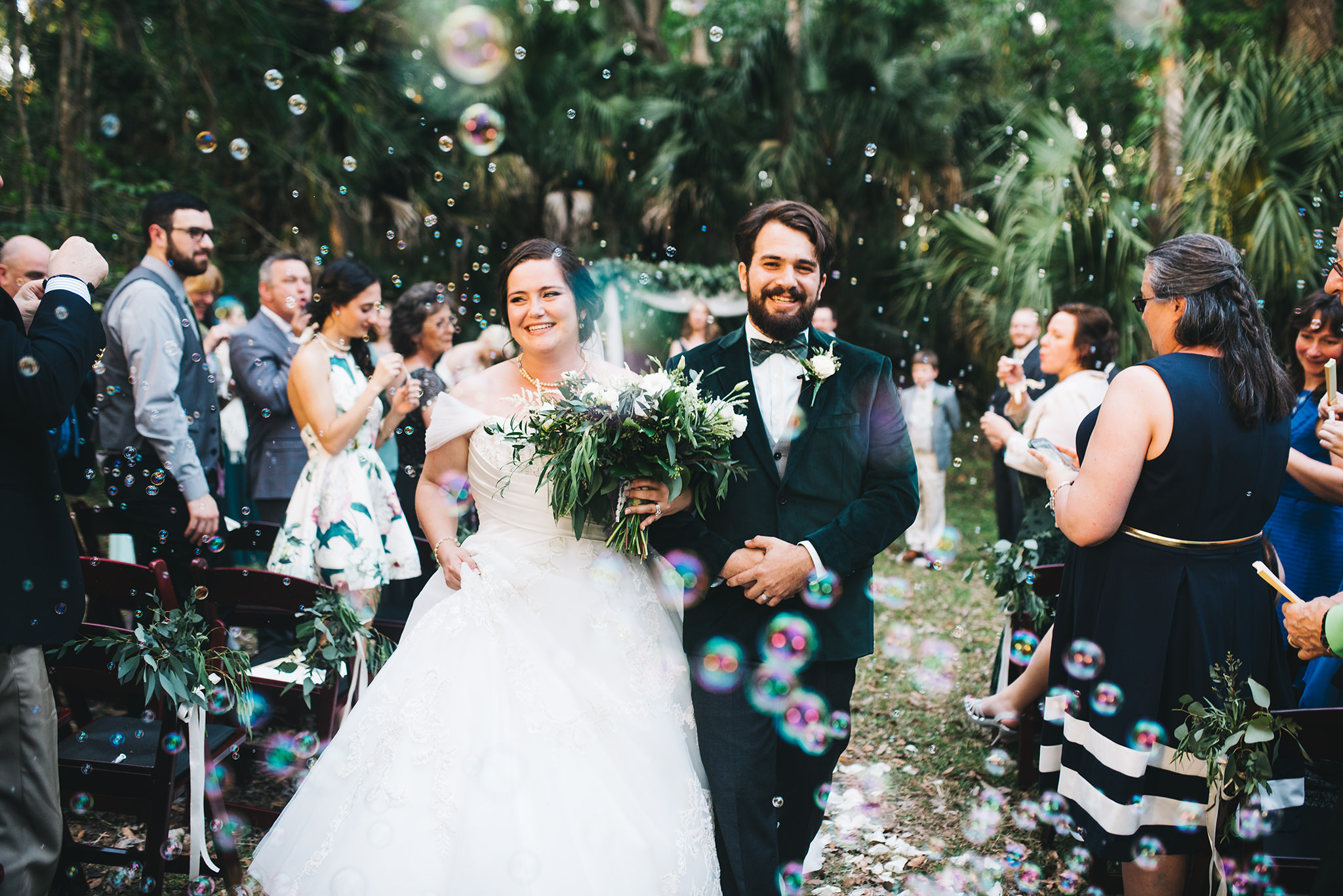 Rudy & Marta Photography - happy newlyweds walking down the aisle among bubbles