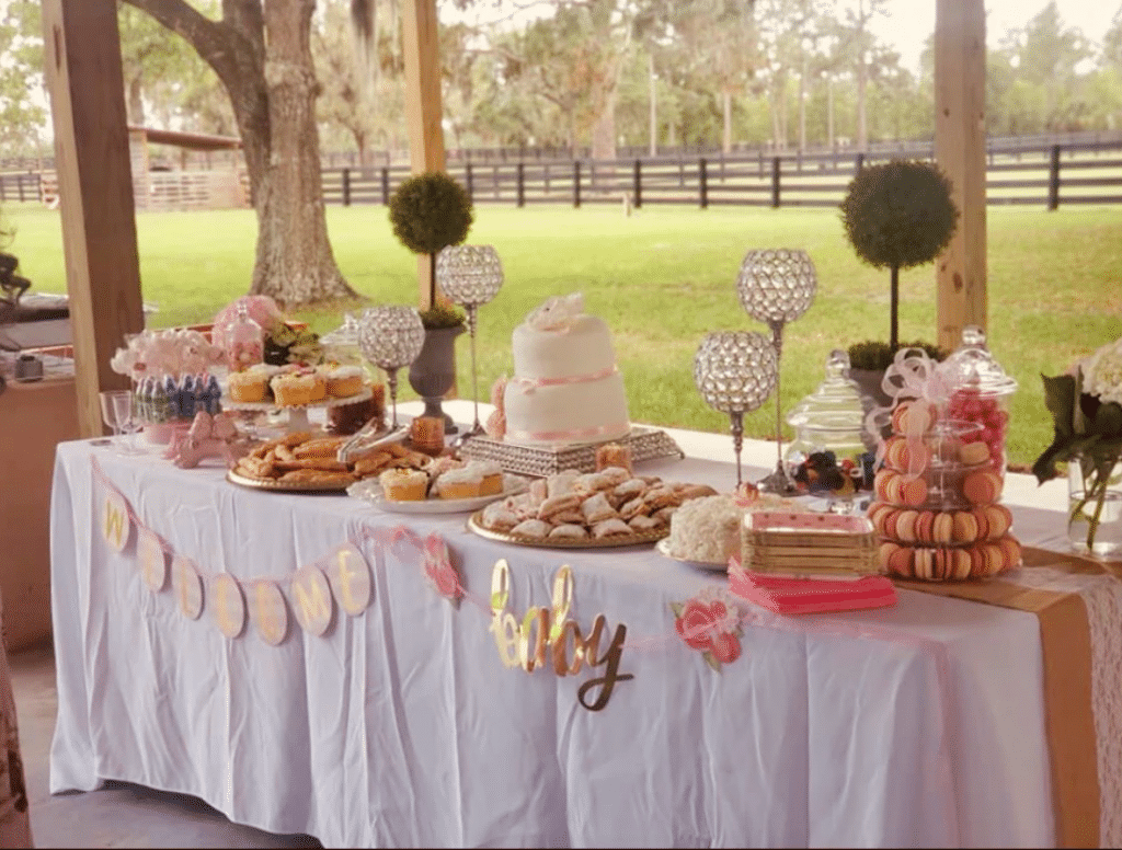 The-Farmhouse-on-44-Table set up with cakes and desserts at a baby shower under outdoor pavilion