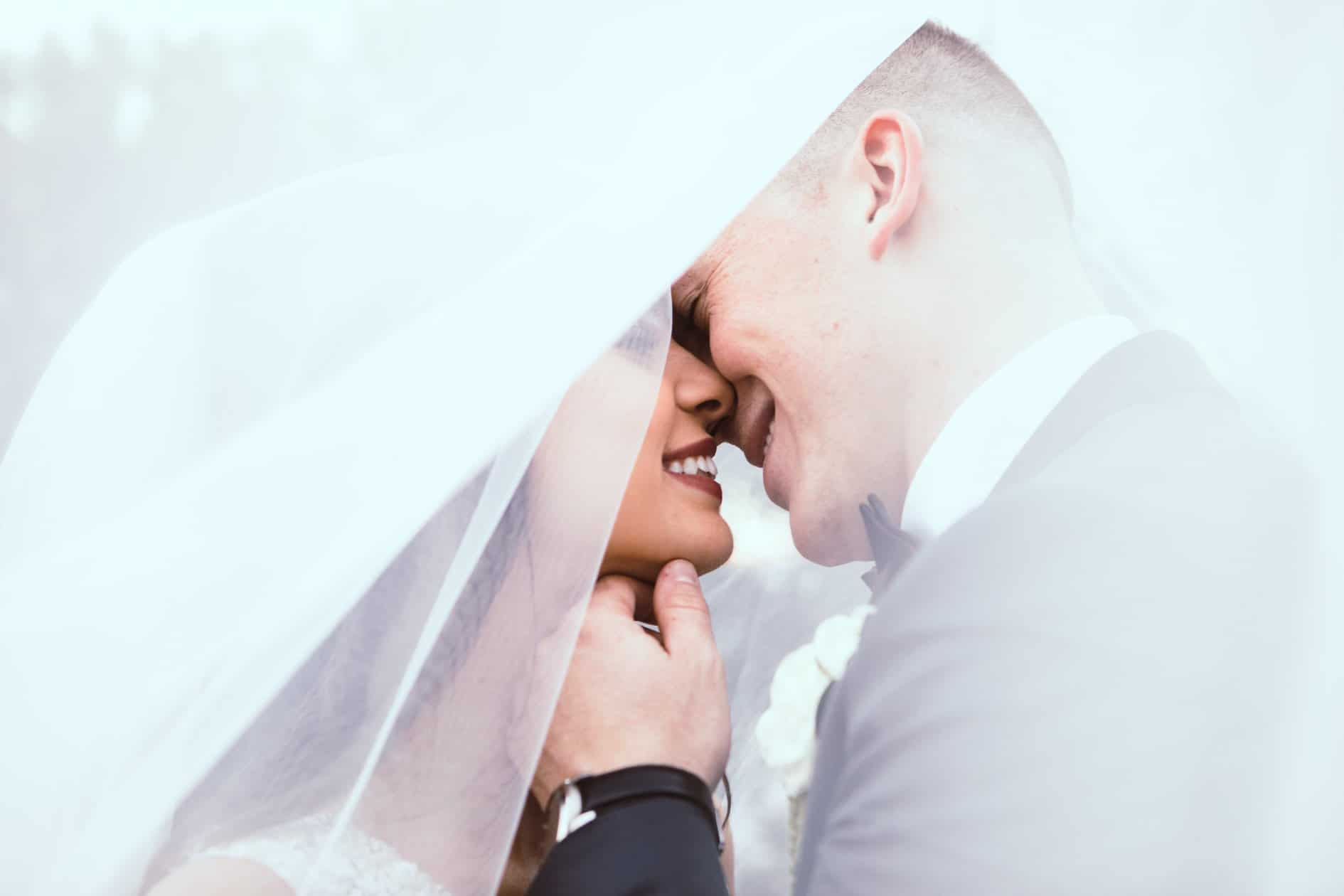 Pearl White Events - bride and groom kissing underneath bride's veil