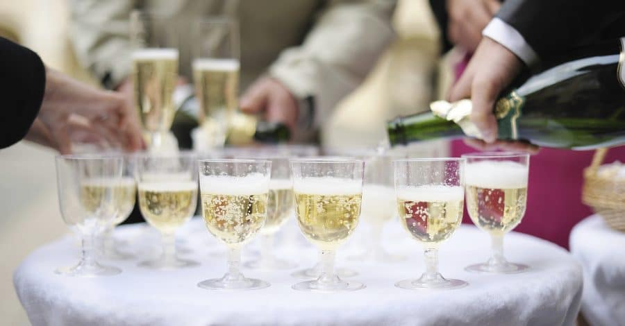 ABC Fine Wine - Glasses of champagne with blurred people standing around the table