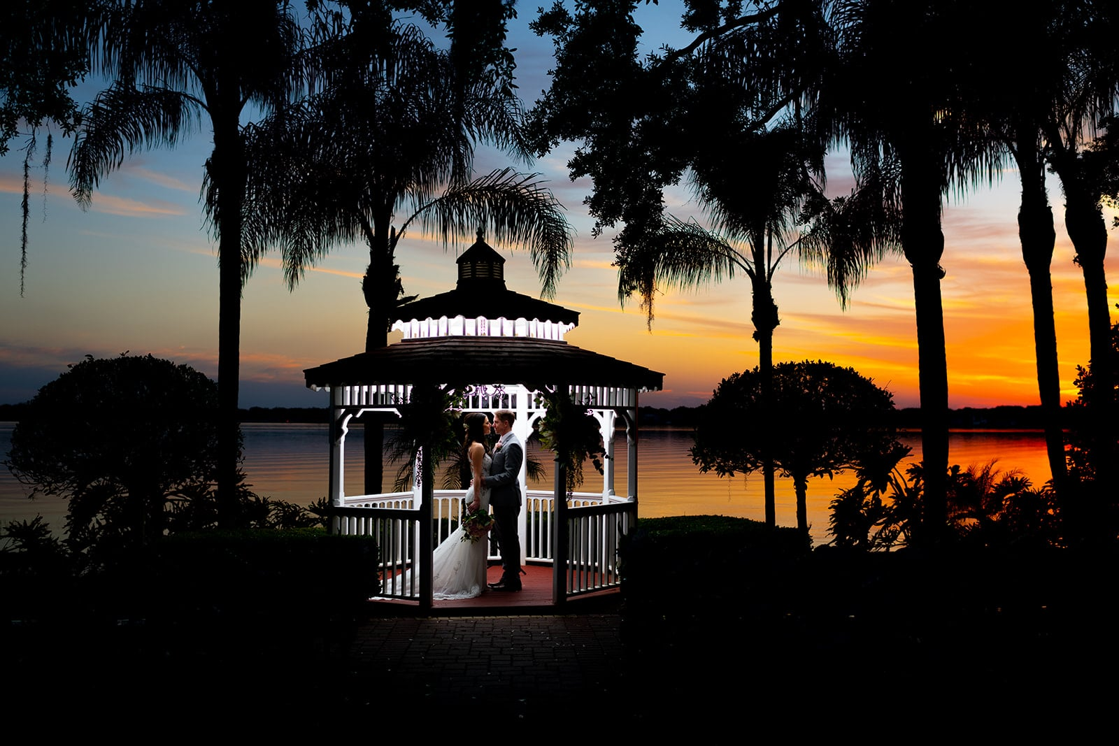Chynna Pacheco Photography - bride and groom under beautifully lit gazebo at sunset