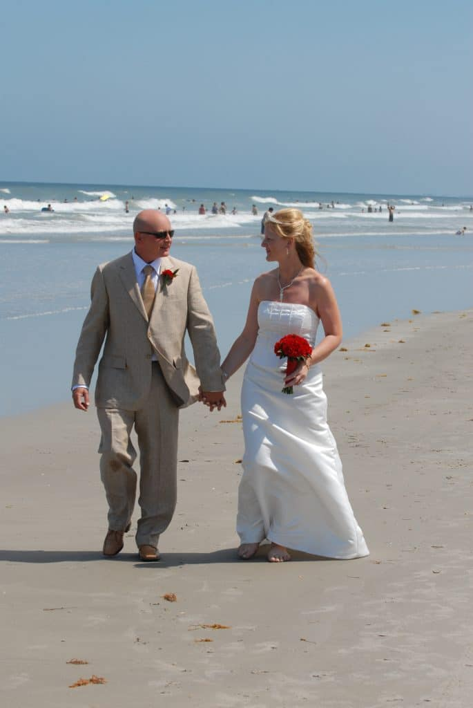 Get Married in Florida - bride and groom walking hand-in-hand on the beach