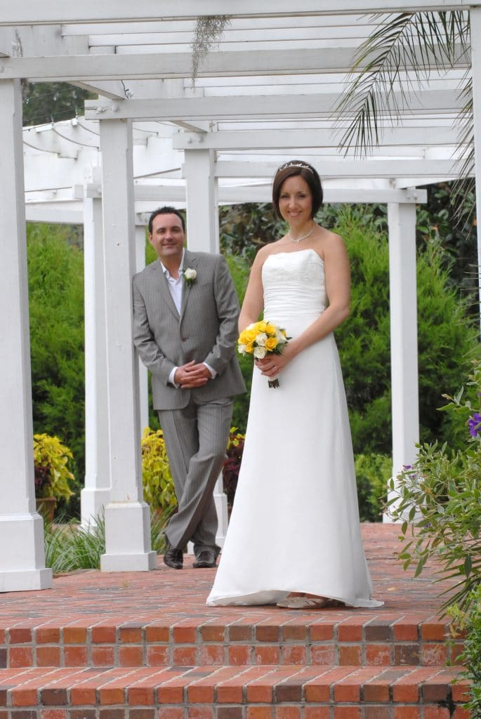 Get Married in Florida - bride under long pergola with groom in background