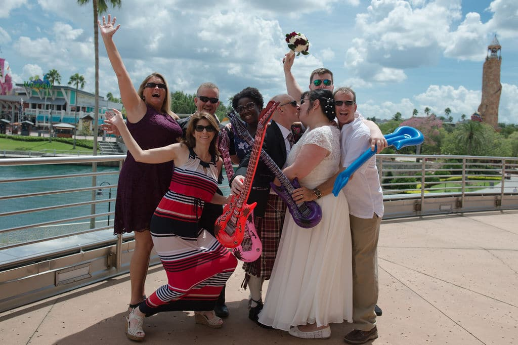 Get Married in Florida - bride and groom kissing at Universal Studios surrounded by friends holding inflatable guitars.