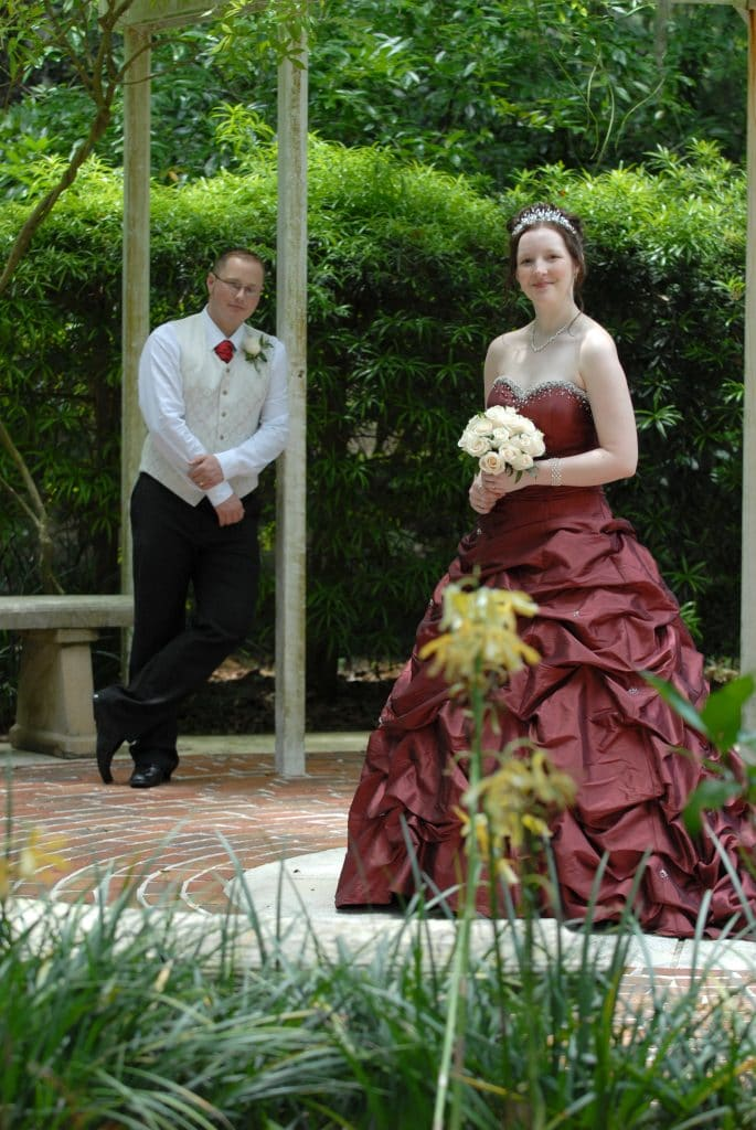 Get Married in Florida - bride in dramatic wine-colored gown posing with groom
