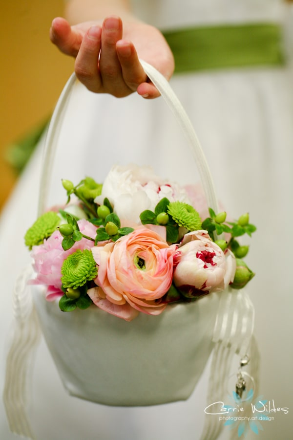 Greenery Productions - flower girl's hand holding white basket with pink and green flowers inside