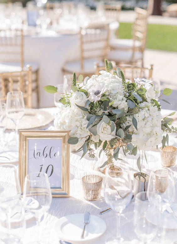 Greenery Productions - small white and green centerpiece next to table marker