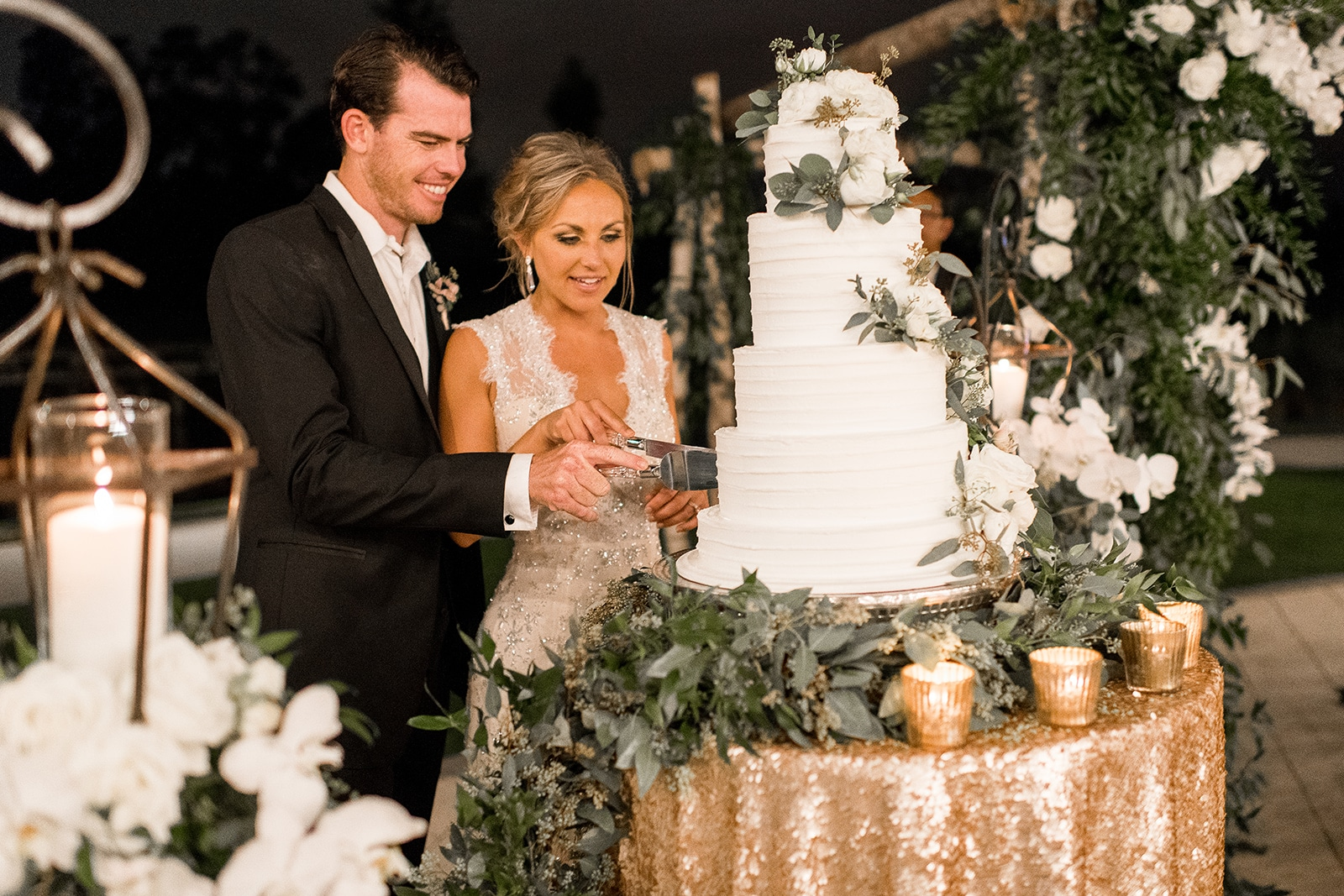 Greenery Productions - couple cutting into wedding cake decorated with white flowers and eucalyptus