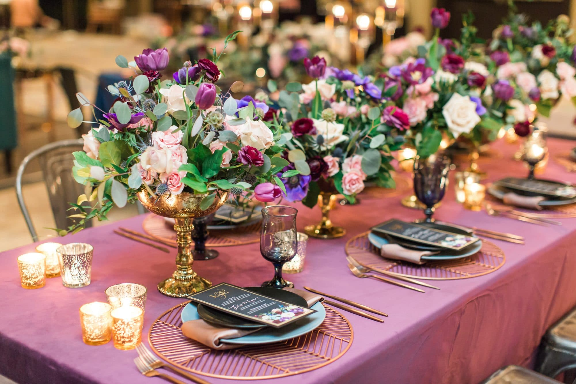 Greenery Productions - purple wedding reception table with row of low purple bouquets in silver goblets