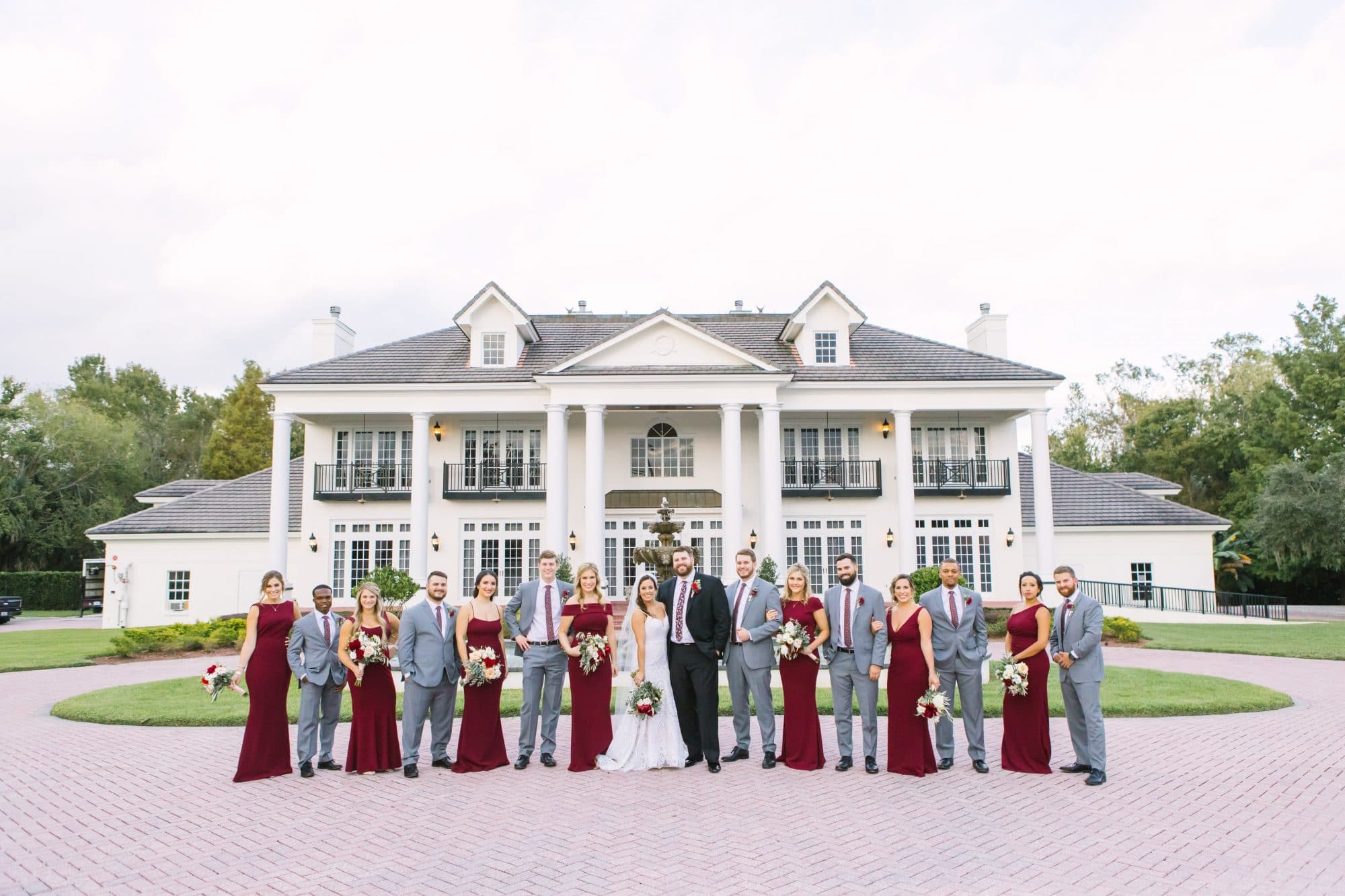 KMD Creations Photography and Film - bride, groom, and wedding party in front of Luxmore Grand Estate