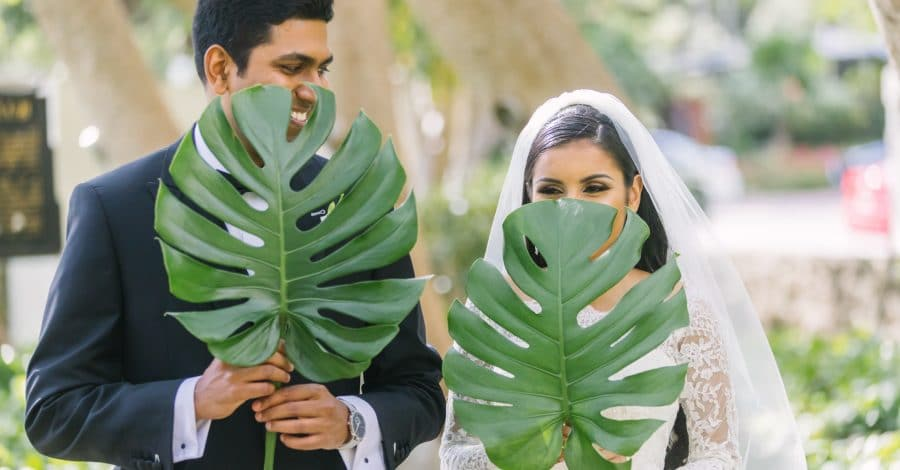 KMD Creations - Bride and Groom holding large palm leaves in front of faces
