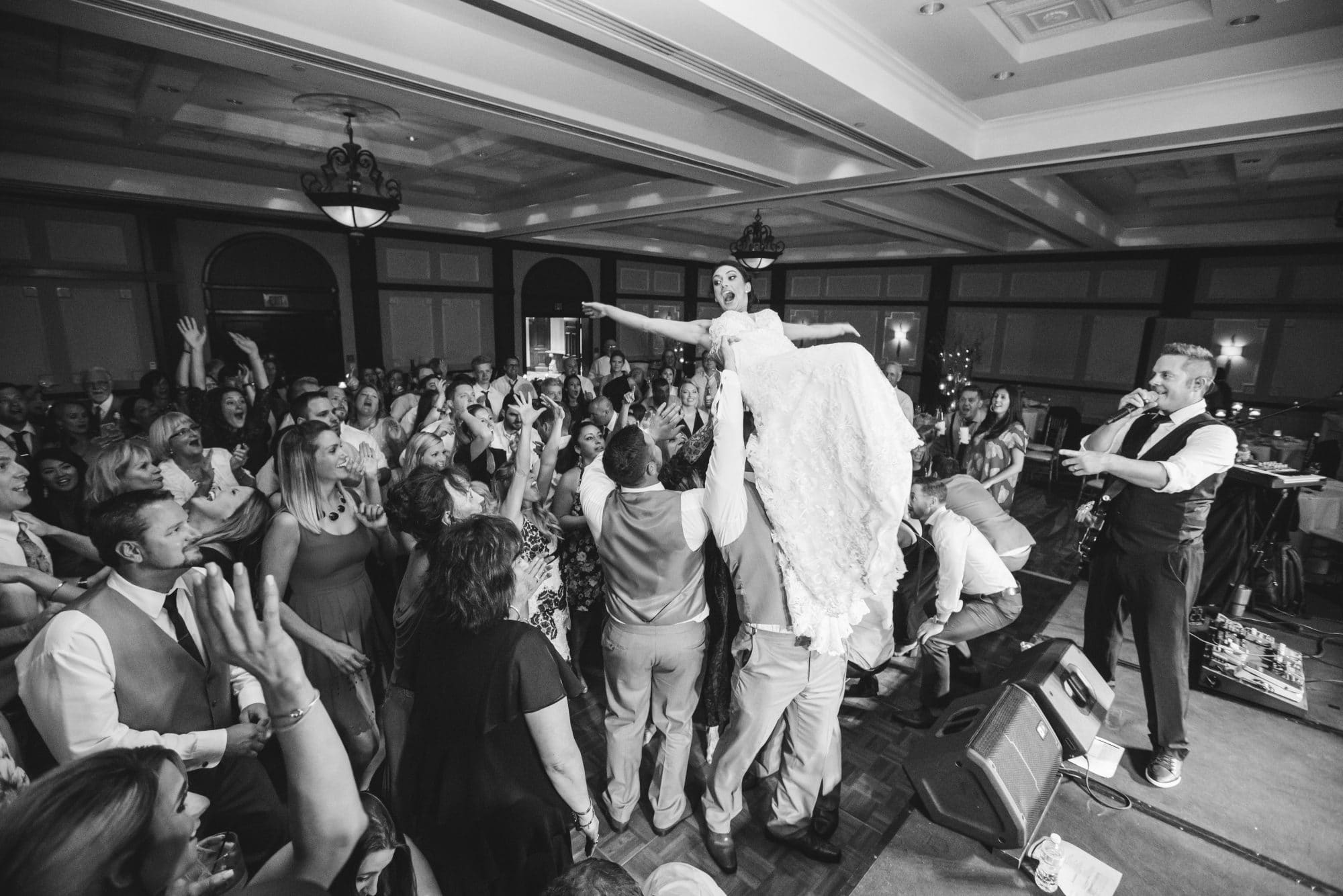 KMD Creations Photography and Film - bride crowdsurfing at wedding reception while band member sings