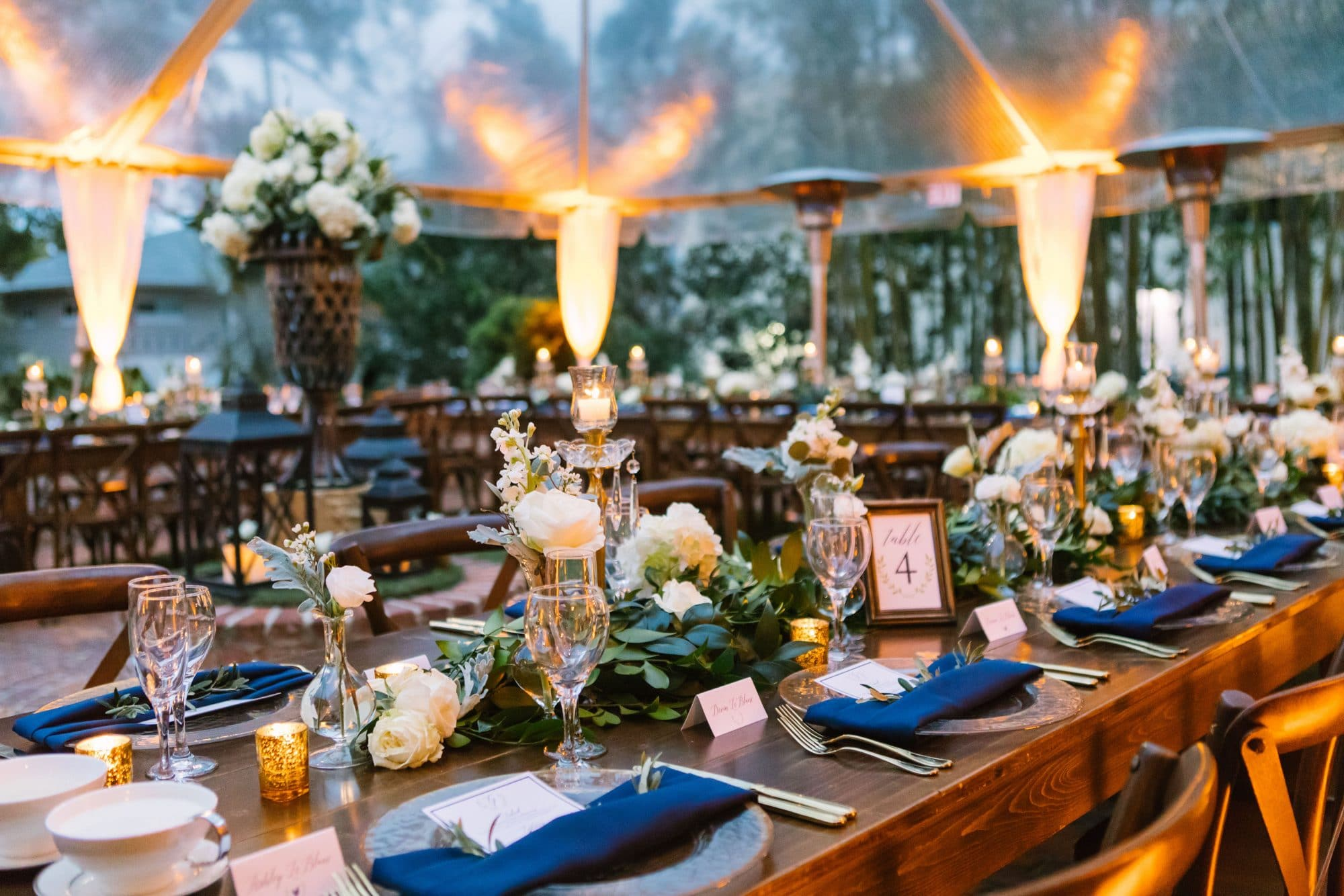 KMD Creations Photography and Film - wedding reception tables with fiery uplighting under transparent event tent