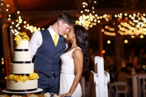 Paradise Cove - newlyweds kissing next to black and yellow wedding cake