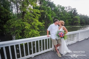 Paradise Cove - casual bride and groom kissing on bridge over lake