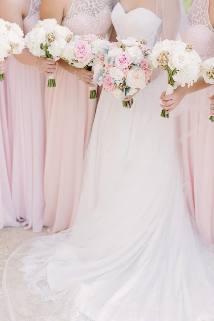 Pearl White Events - bride and bridesmaids holding pastel bouquets in a row