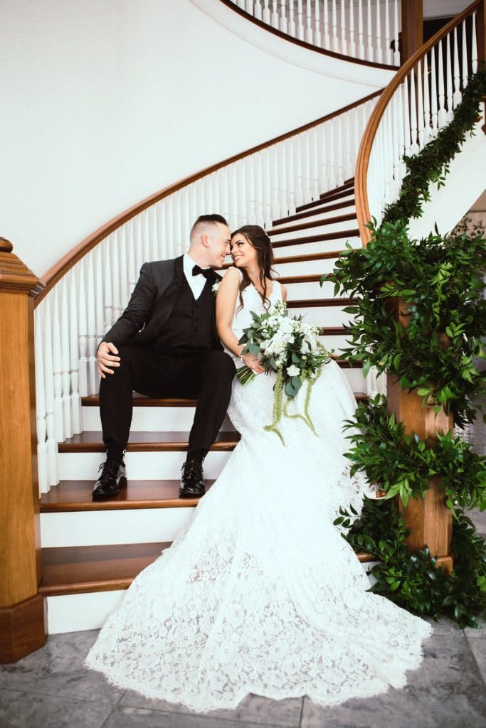 Pearl White Events - bride and groom sitting beside each other on beautiful curved staircase