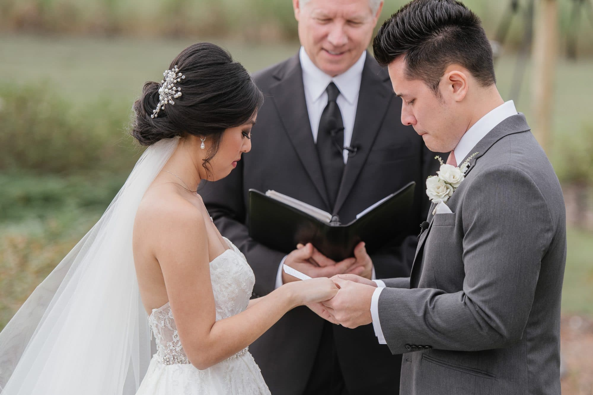 Pearl White Events - attractive Asian bride and groom holding hands during wedding ceremony
