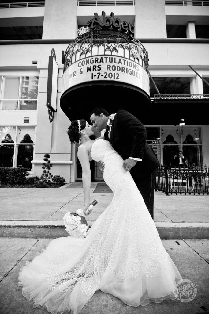 Sugar Pop Productions- bride & groom kissing under congratulations sign on building