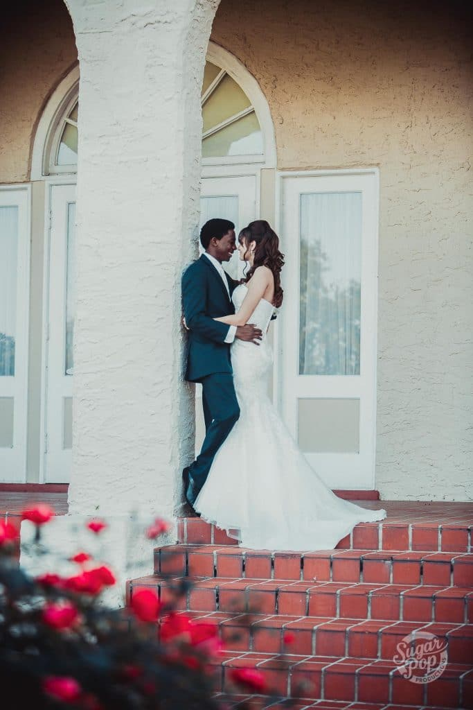 Sugar Pop Productions - bride & groom standing against column on porch