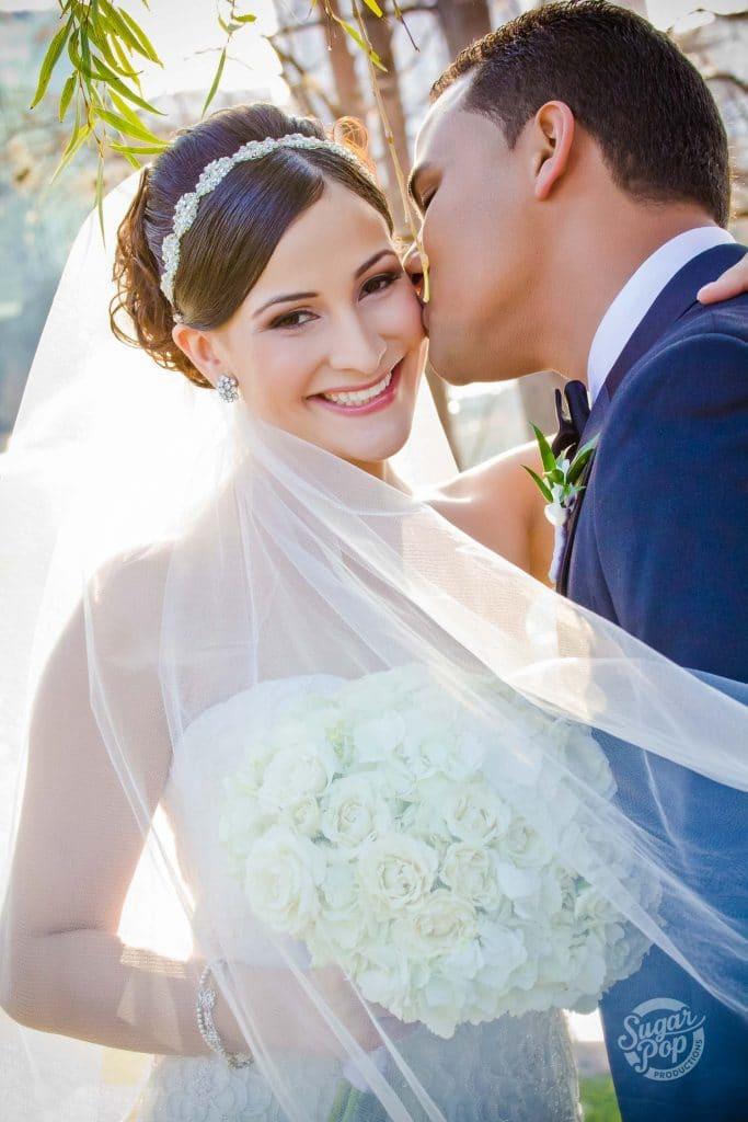 groom kissing bride's cheek with veil flowing outside