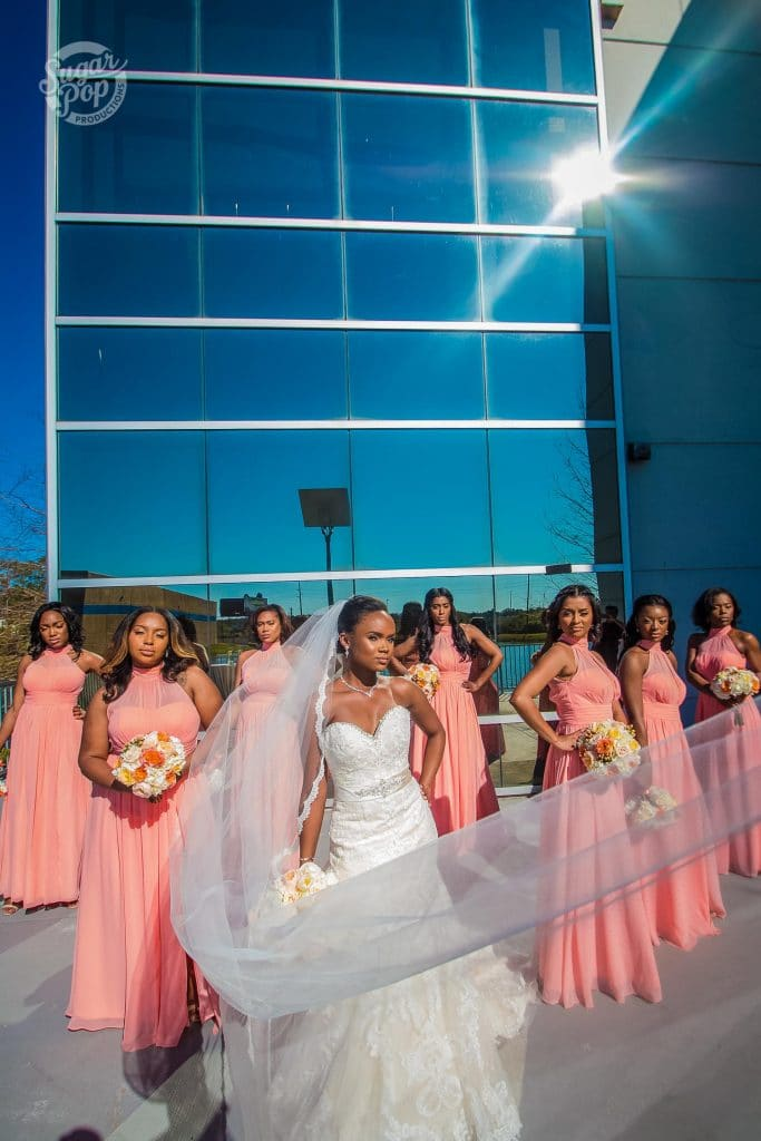 Sugar Pop Productions- bride with bridal party outside of building with sun reflection