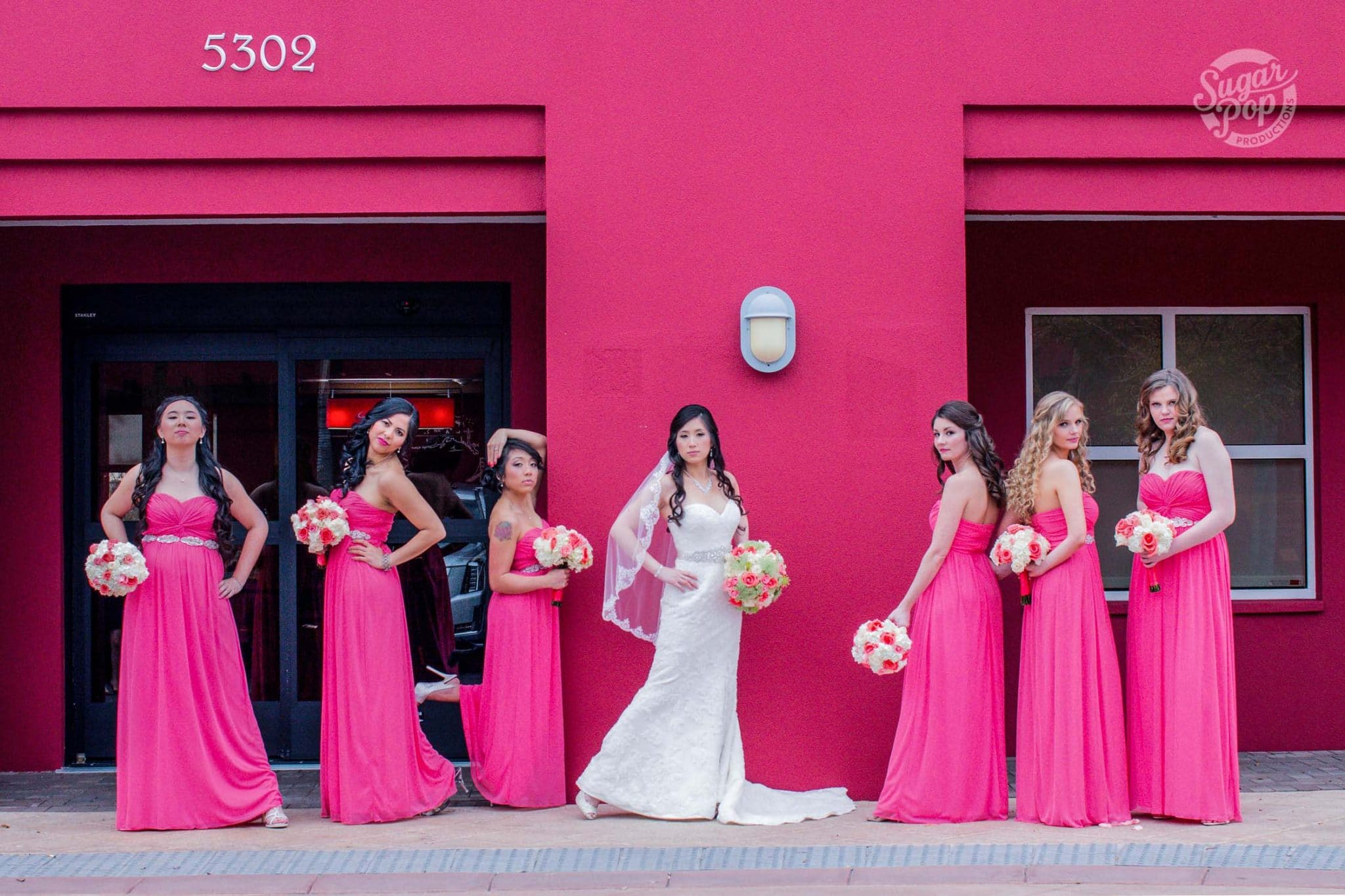 Sugar Pop Productions - bride with bridesmaids in pink standing in front of pink building