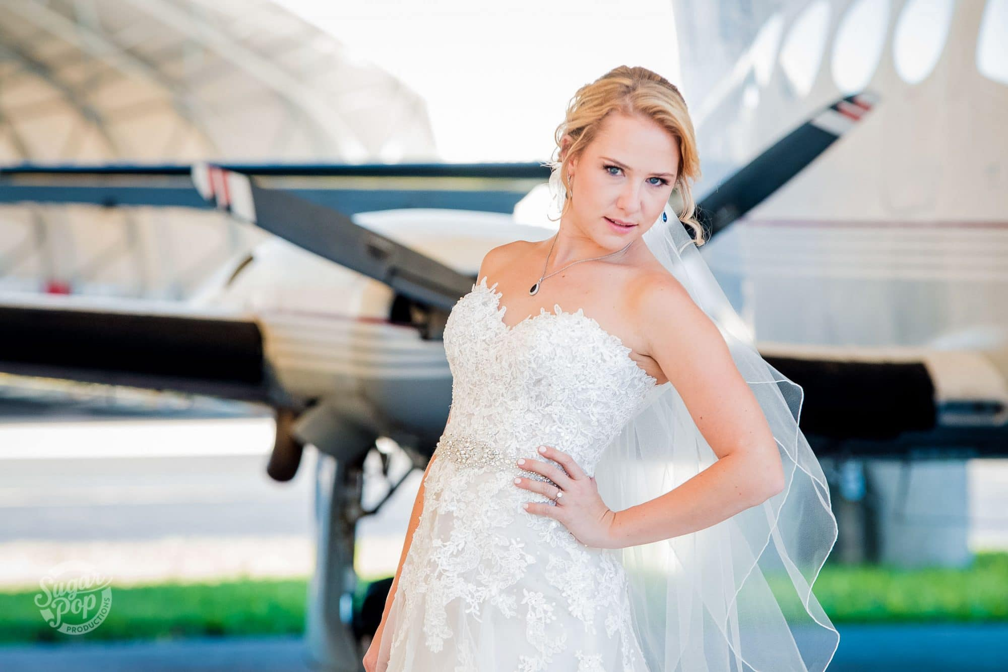 Sugar Pop Productions - bride in front of small plane