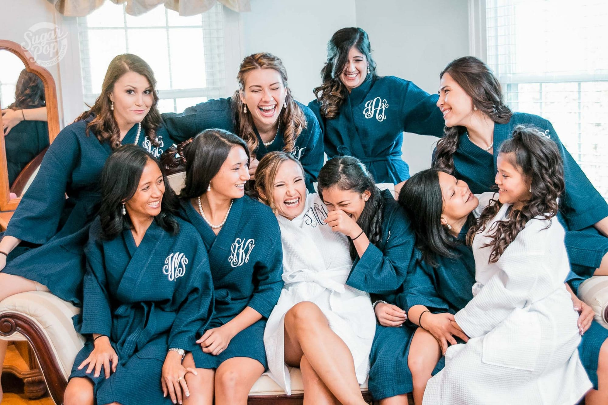Sugar Pop Productions - bride and bridesmaids lounging on couch in matching robes