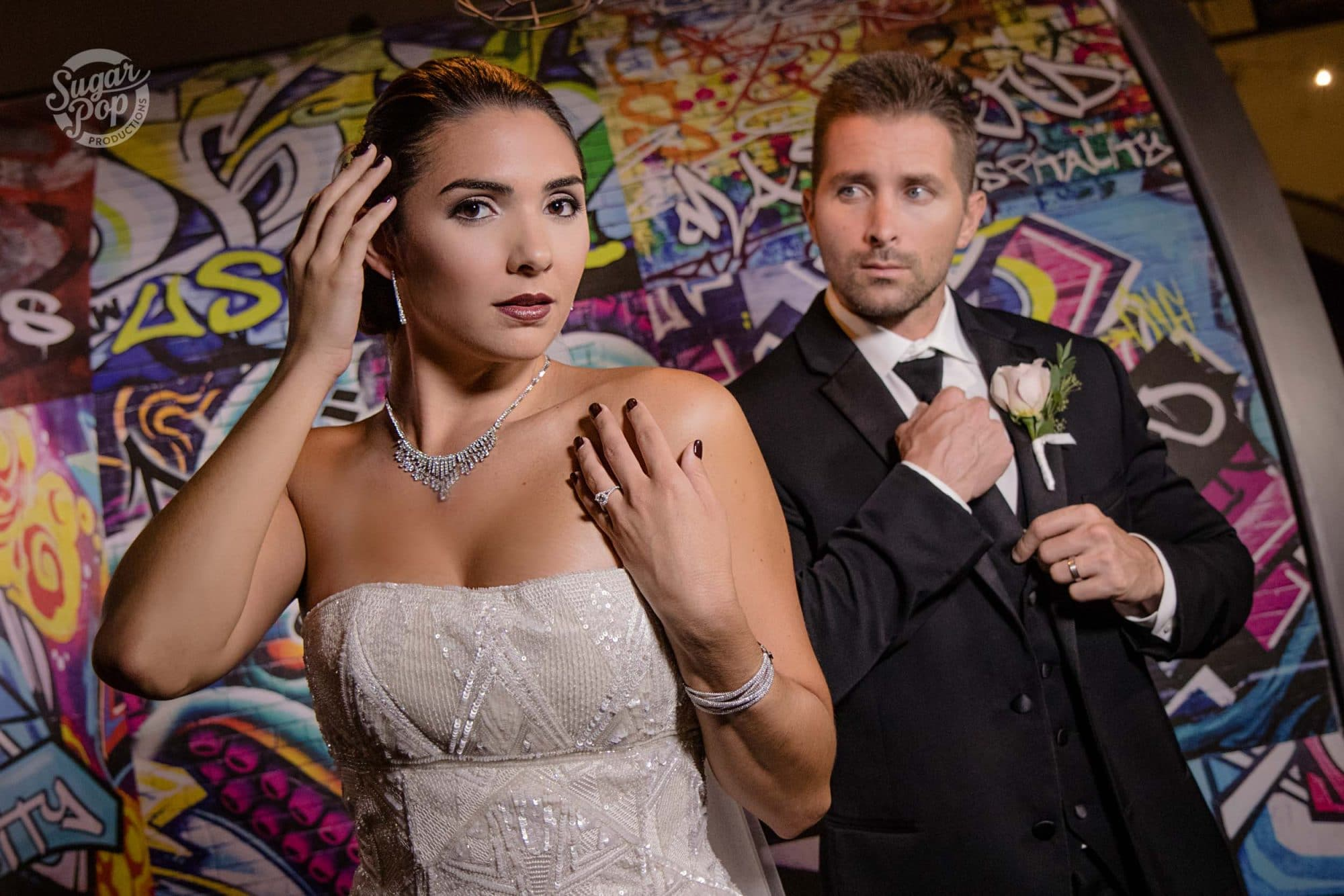 Sugar Pop Productions - bride and groom in front of graffiti wall
