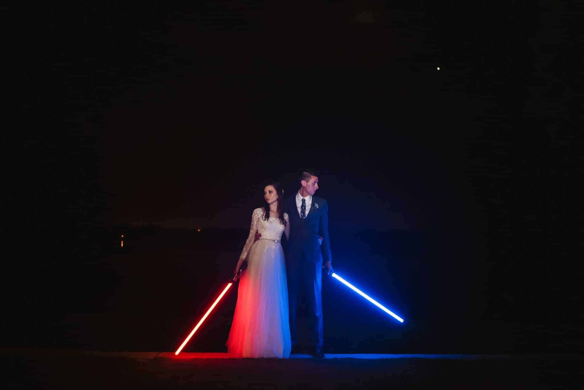 Blue Blazers Entertainment - Bride and groom holding light sabers in pitch black