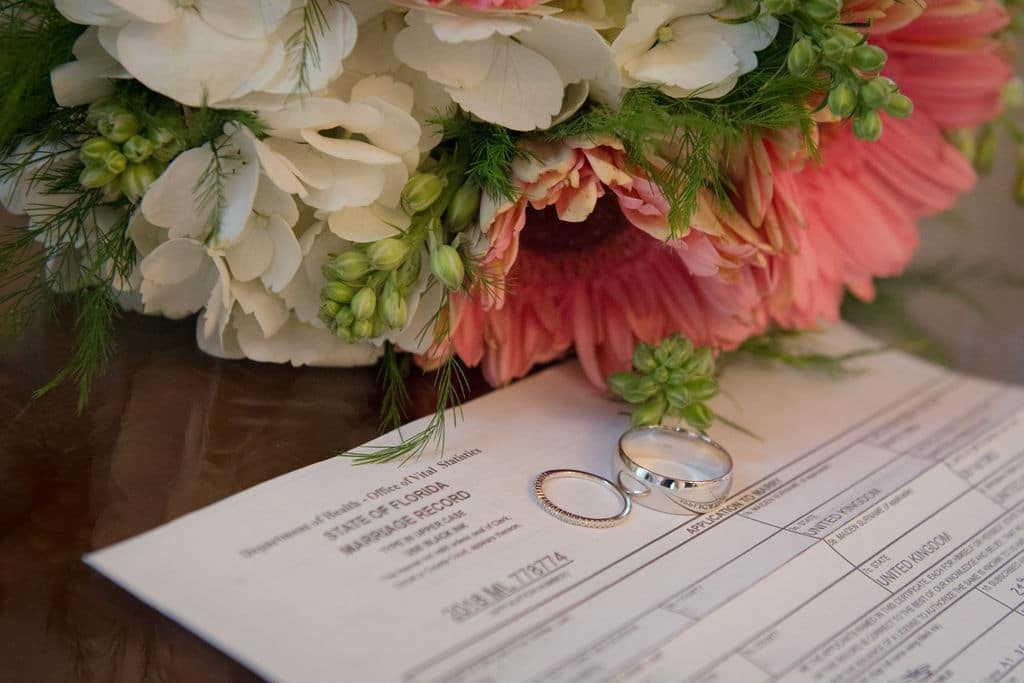 Florida Marriage License by Mail, bouquet and rings sitting on marriage license