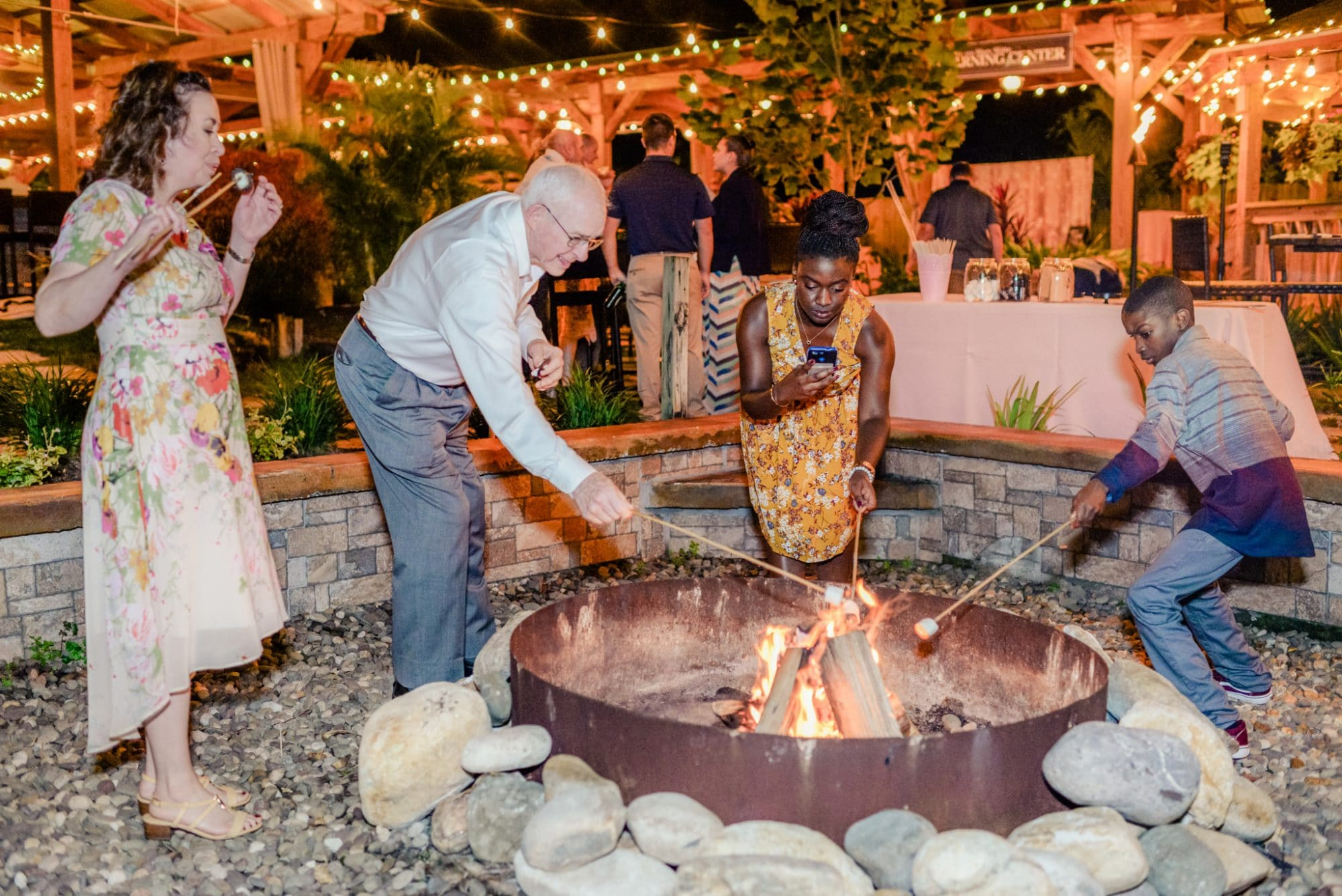Rockledge Gardens - wedding guests making s'mores around outdoor firepit