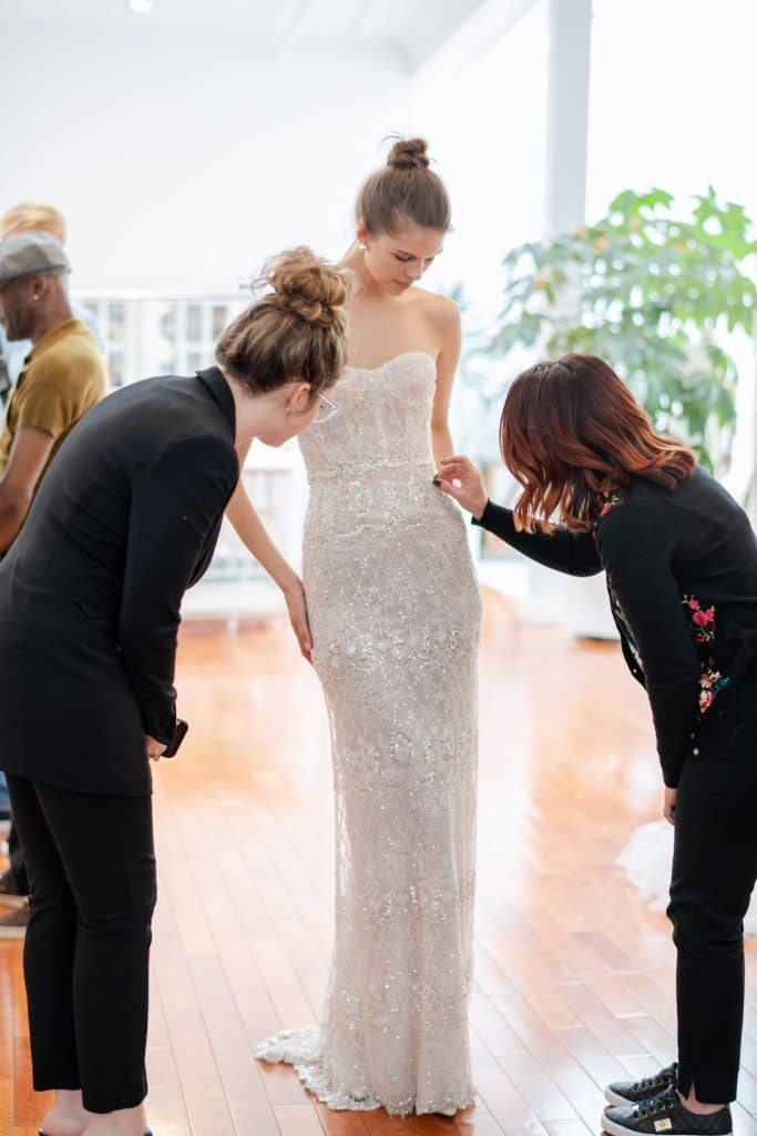 Solutions Bridal - wedding planners making adjustments to slim bridal gown
