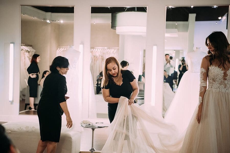 Solutions Bridal - two saleswomen examining train on bridal gown
